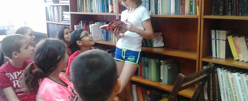 Доброволката Веселина Пепеланова занимава малчуганите с четене в Библиотеката